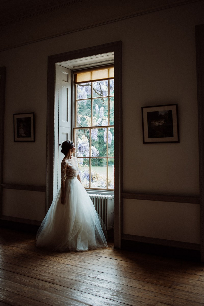 Bride standing looking out of the window at Fulham Palace