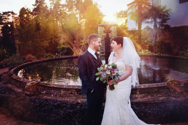 Bride and groom by fountain at Le Petit Chateau