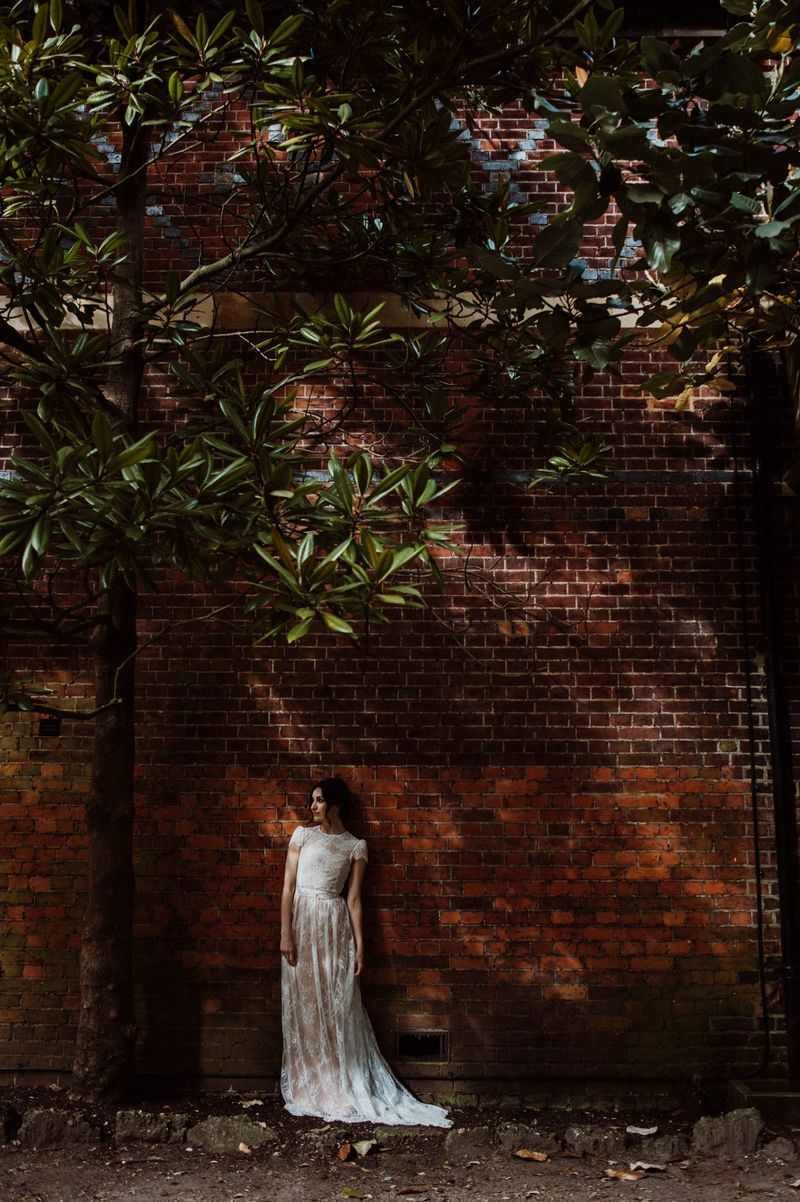 Bride standing next to a wall at Fulham Palace