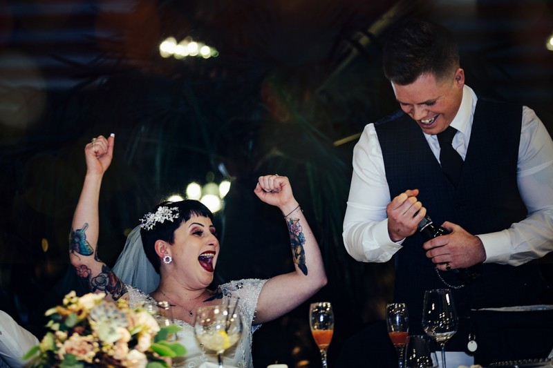 Bride with arms in the air during best man speech