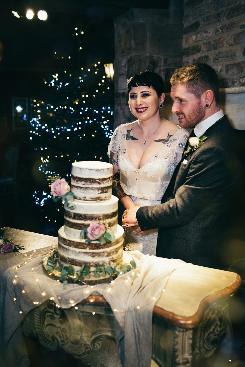 Bride and groom cutting naked wedding cake