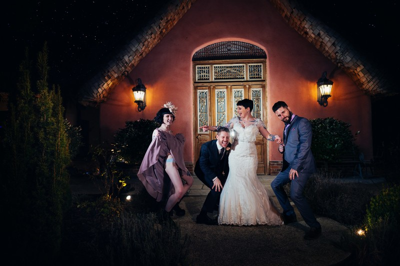 Bride and groom with friends outside Le Petit Chateau at night