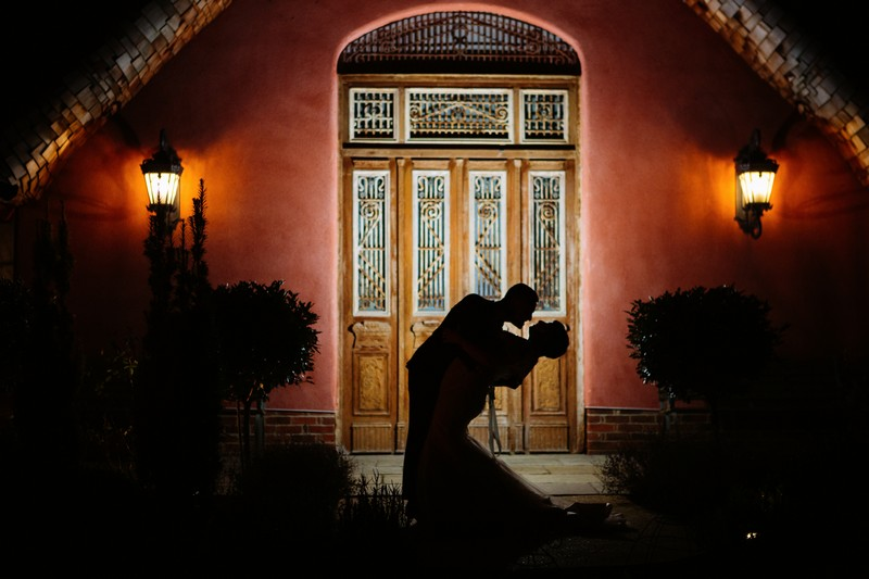 Silhouette of bride and groom outside Le Petit Chateau at night