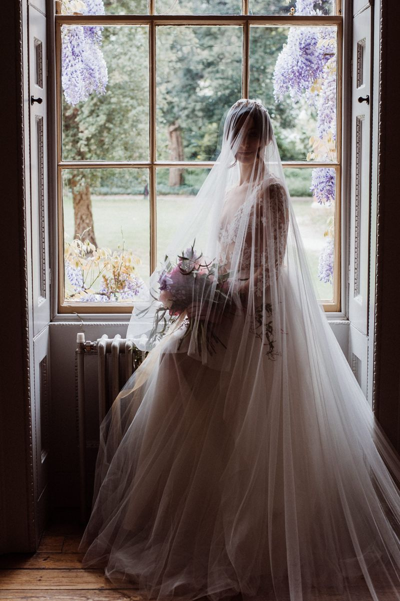 Bride with long veil standing by window at Fulham Palace