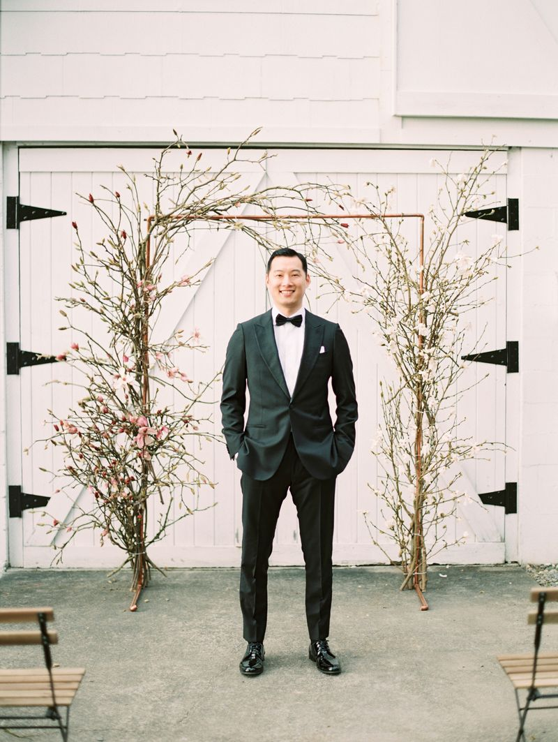 Groom standing in front of magnolia floral ceremony arch