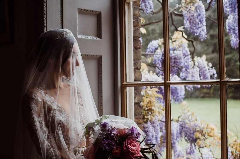 Bride with long veil looking out of the window at Fulham Palace