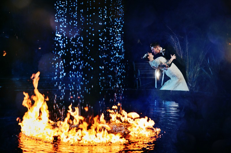 Bride and groom by fountain with fire around it at Le Petit Chateau