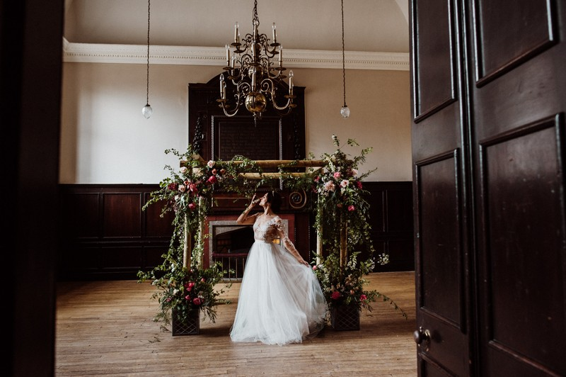 Bride in front of chuppah covered in foliage and peonies