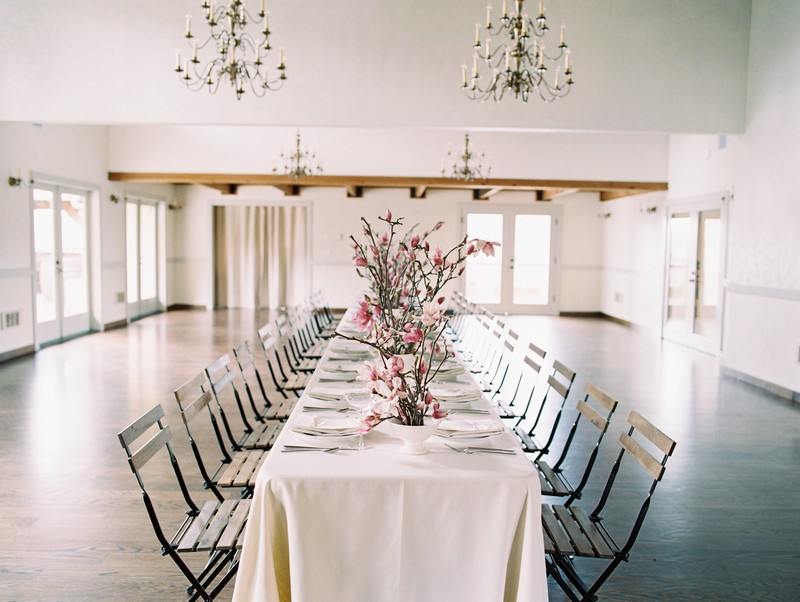Long wedding table styled with pink magnolia flowers