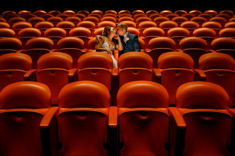 Bride and groom sitting on theatre seating - Picture by Damion Mower Photography