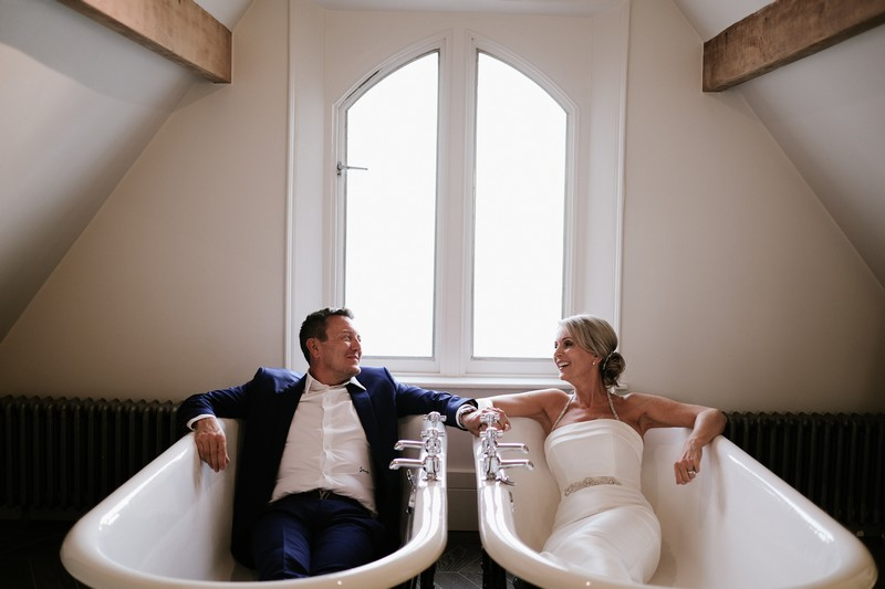 Bride and groom sitting in bathtubs - Picture by Rebecca Parsons Photography