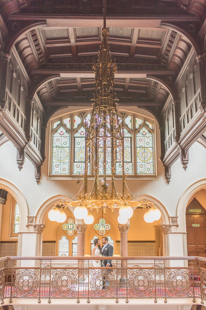 Bride and groom standing under large, elaborate light in grand wedding venue - Picture by Tanya Flannagan Photography