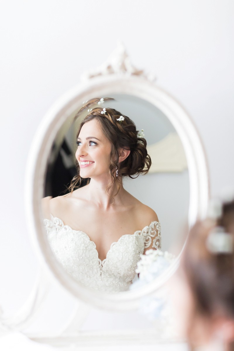 Reflection in mirror of bride looking to the side and smiling - Picture by First Light Photography