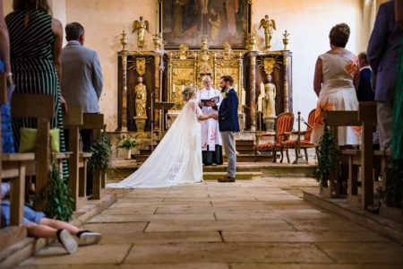 Young boy's legs poking out of seating onto aisle during wedding ceremony - Picture by Jonny Barratt Photography
