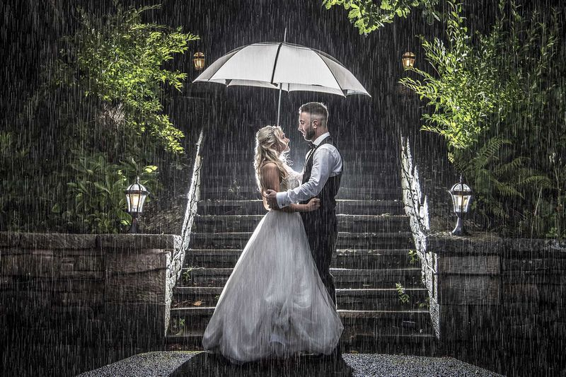 Bride and groom standing under umbrella in the rain - Picture by Peter Anslow Photography