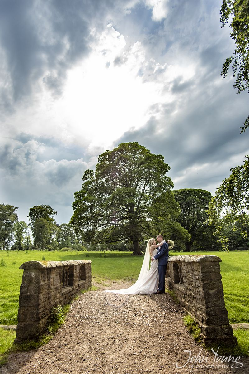 Bride and groom on small bridge with tress in the background - Picture by John Young Photography