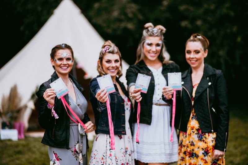 Girls holding passes for festival hen party