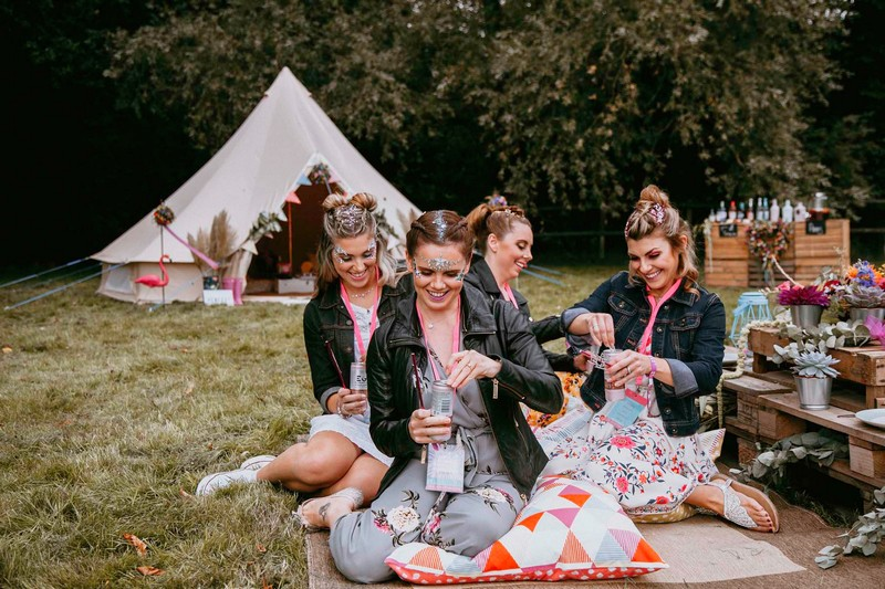 Girls sitting on rug at hen party opening drinks