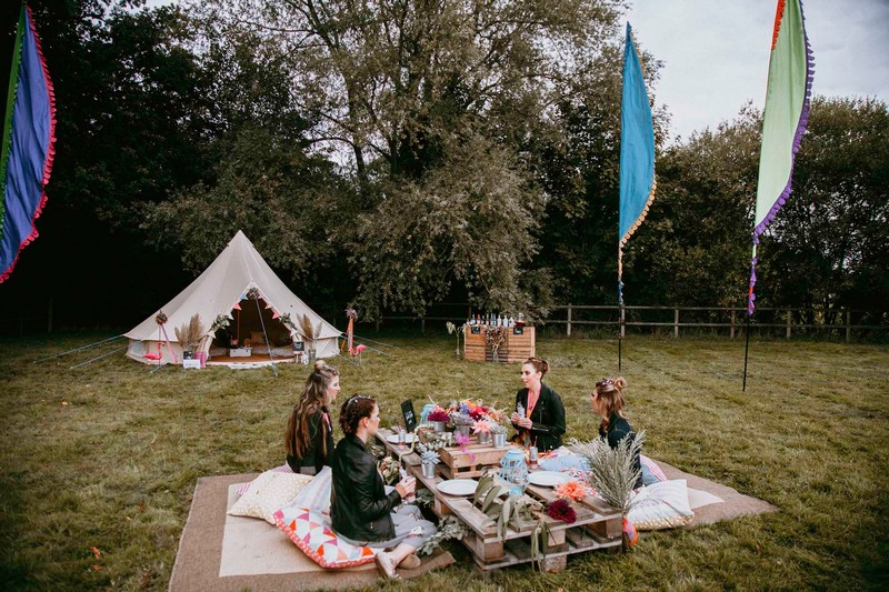 Festival hen party outside with girls sitting at pallet seating area