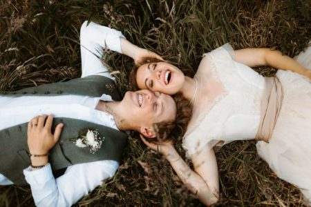 Bride and groom laying in grass with their heads touching - Picture by The Hendrys Photography