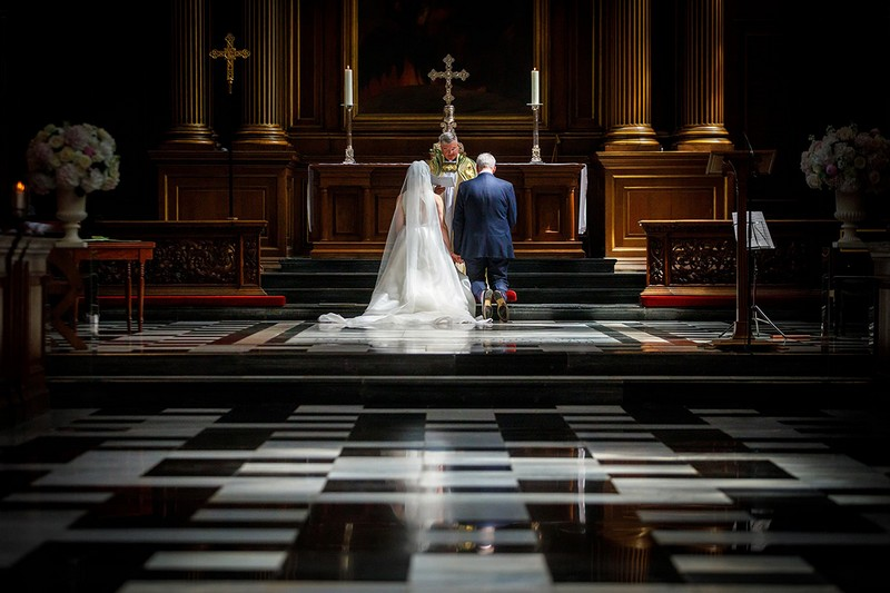 Bride and groom nealing at altar in front of priest - Picture by Duncan Kerridge Photography