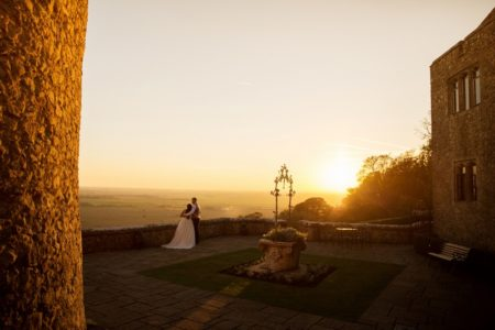 Bride and groom looking at view from courtyard of wedding venue as sun sets - Picture by Helen England Photography