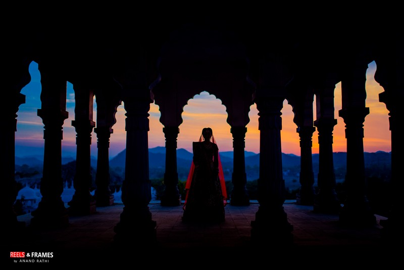 Silhouette of bride standing between pillars of wedding venue looking at views of mountains - Picture by Reels and Frames
