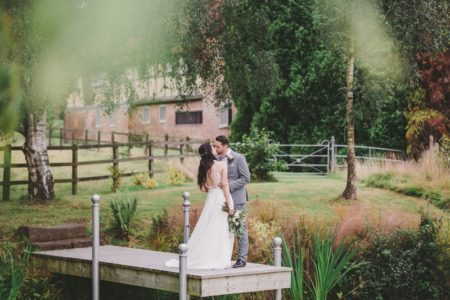 Bride and groom kissing on small jetty in grounds of wedding venue - Picture by Mini and Me Photography