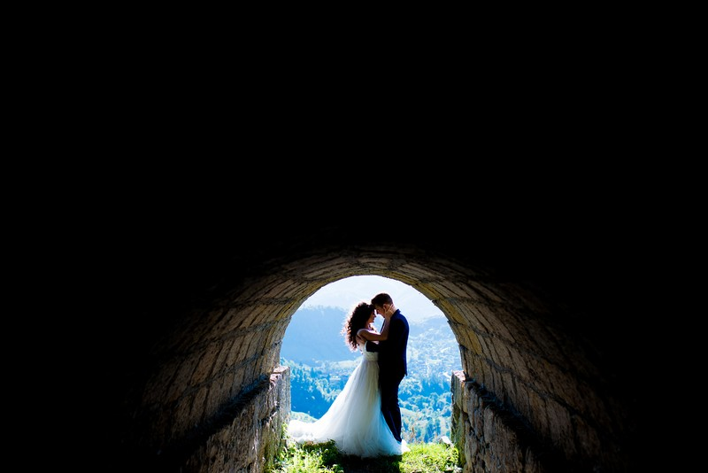 Bride and groom at the end of dark tunnel in front of view of landscape - Picture by Victor Duduca