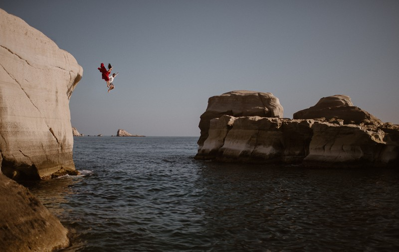 Couple jumping off cliff into the sea - Picture by Adventure Instead