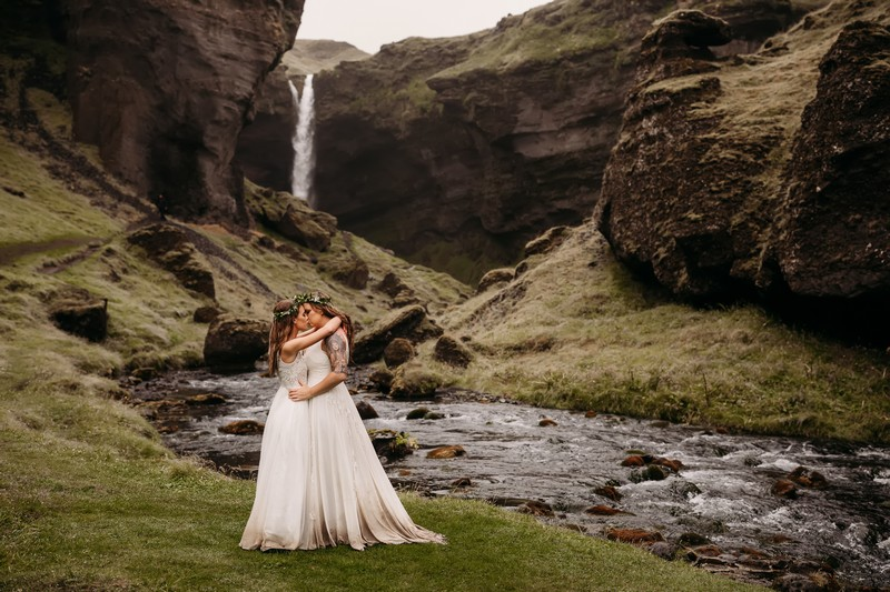 Brides kissing by stream in valley - Picture by Vee Taylor Photo