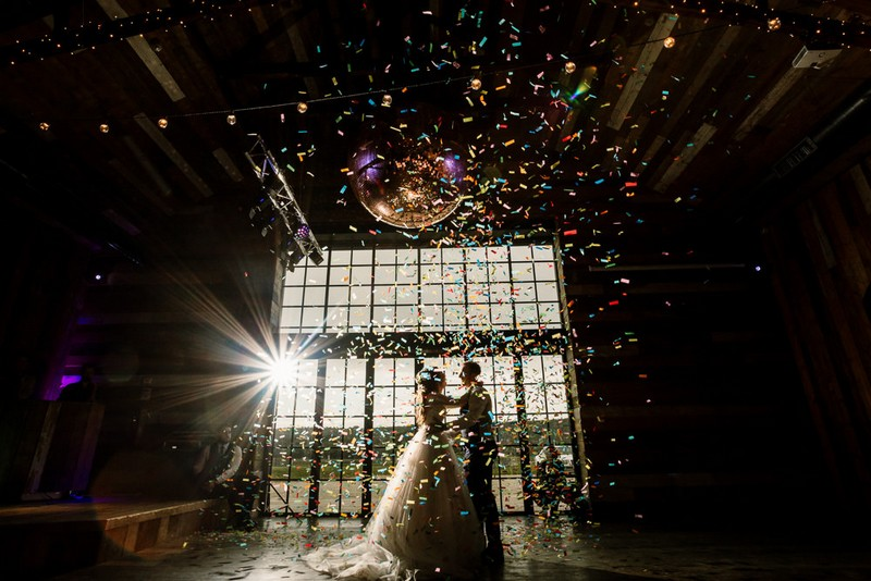 Bride and groom on dance floor as confetti falls around them - Picture by Hayley Baxter Photography