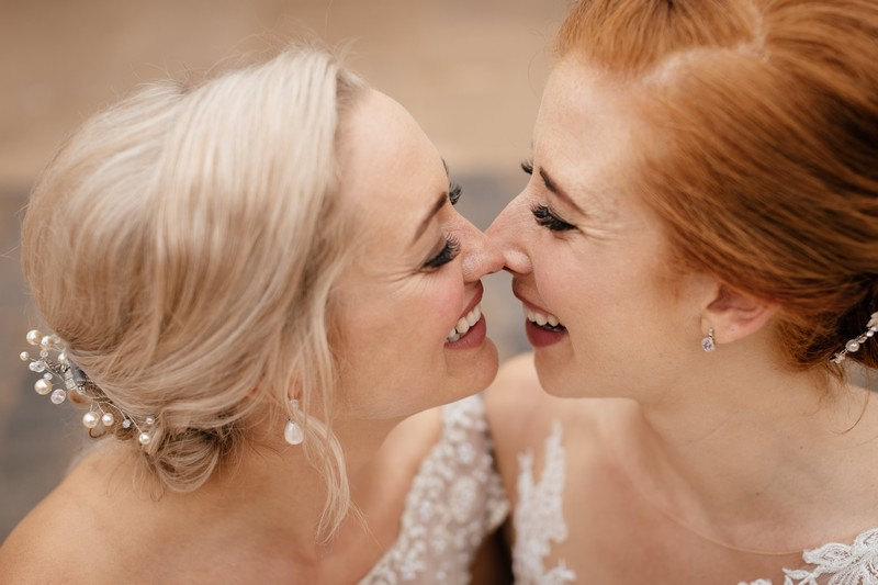 Two smiling brides touching noses - Picture by Jules Barron