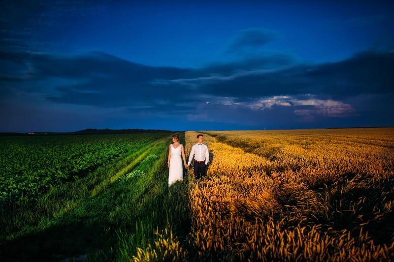 Bride standing on side of field with green grass and leaves holding hands with groom on side with golden wheat - Picture by Pollok Pictures