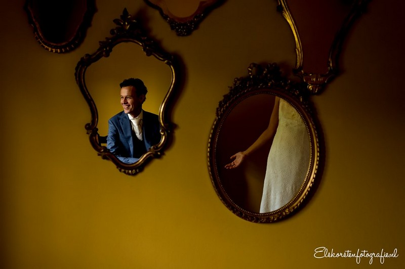 Mirrors on wall showing reflections of groom's head and bride's arm - Picture by Els Korsten Fotografie