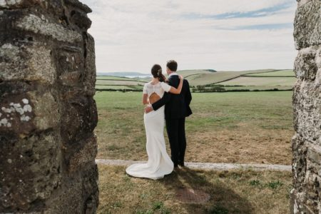 Bride and groom with arms on each others backs looking at view across field - Picture by Alexa Poppe Wedding Photography