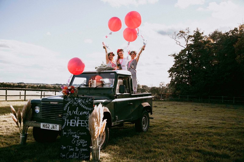 Henfest sign in front of girls standing on back of Land Rover holding balloons