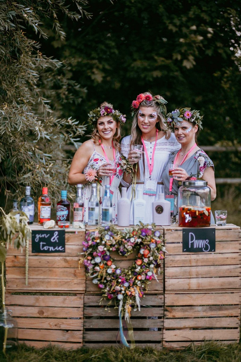 Girls at hen party standing behind pallet gin bar