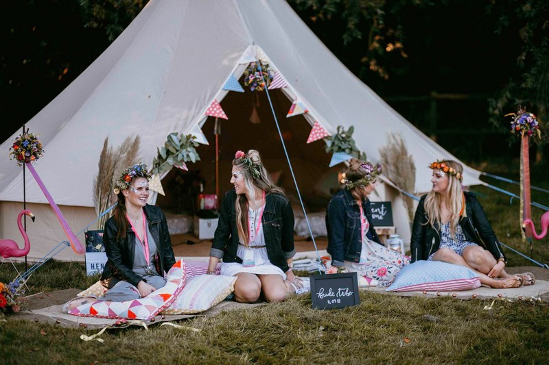 Girls sitting in front of tipi at festival hen party
