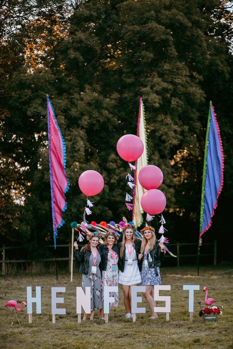 Girls behind Henfest letters with balloons and festival flags