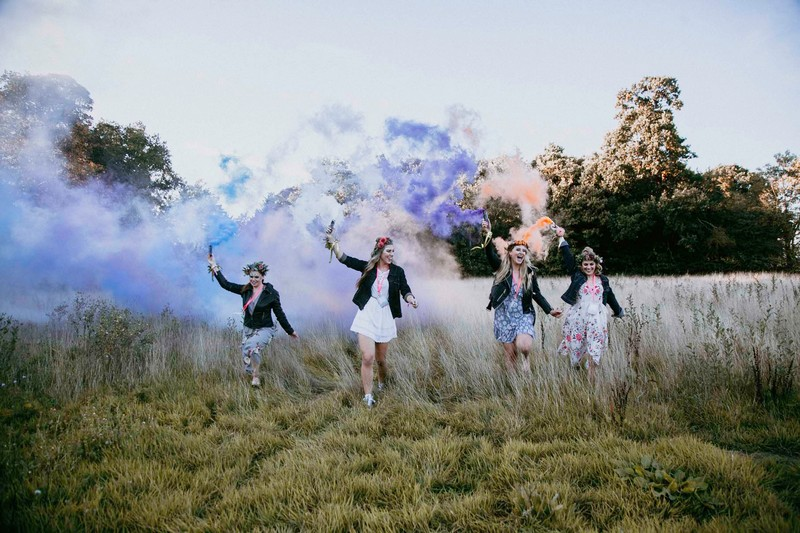 Girls at hen party walking across field with smoke bombs