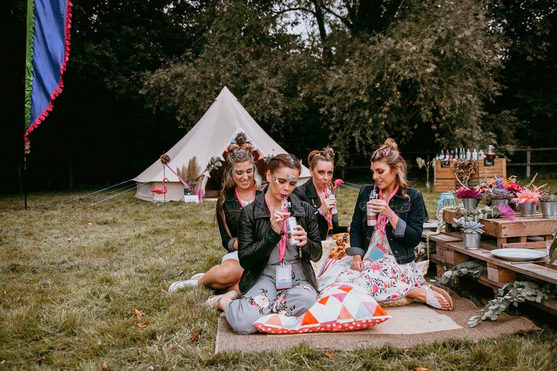 Girls at festival hen party sitting on rug
