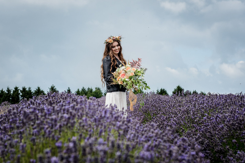 Bride wearing leather jacket in lavender field