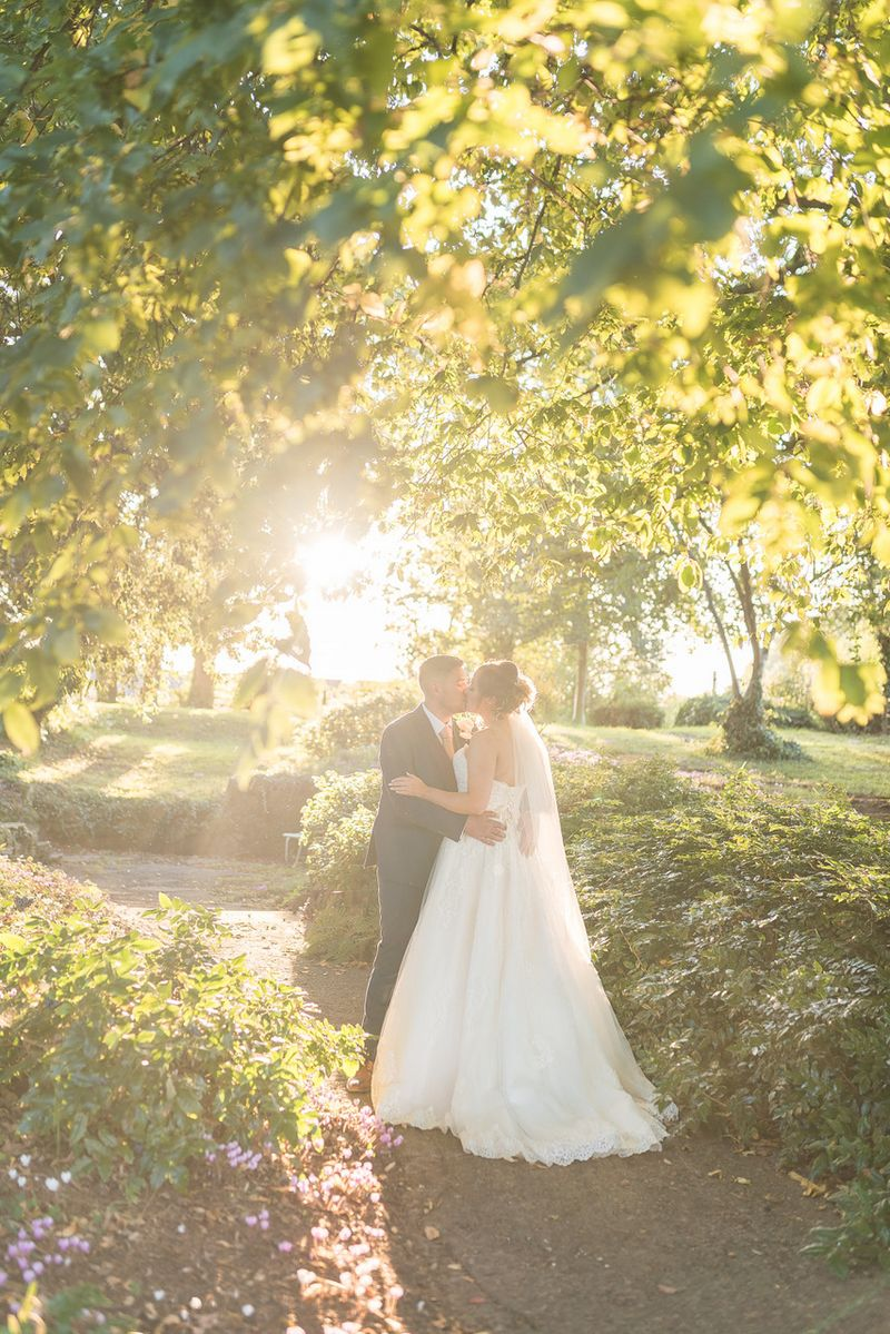 Bride and groom kissing under trees in hazy sunshine - Tanya Flannagan Photography