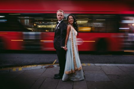 Bride and groom standing back to back with blurred red bus in background - Picture by Kevin Belson Photography