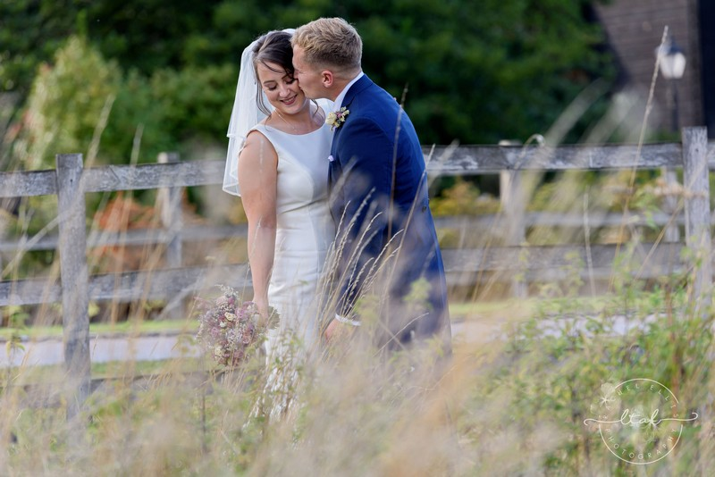 Groom kissing bride on cheek in field - Picture by Life Through A Lens - Rachel Ellis Photography
