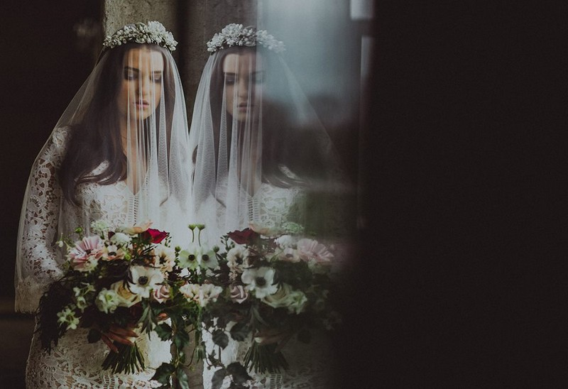 Bride leaning against window showing her reflection - Picture by Loke Roos