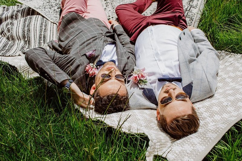 Two grooms with sunglasses on laying down next to each other on a rug - Picture by When Charlie Met Hannah