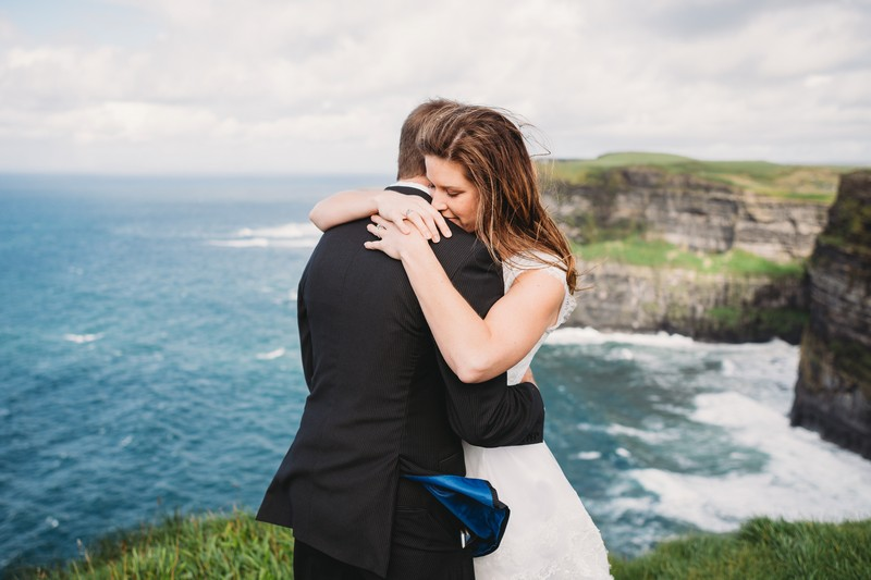 Bride and groom hugging in front of sea - Picture by Lisa Lander Photography