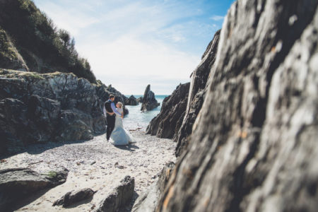 Bride and groom on beach amongst rocks - Picture by Andrew George Photography